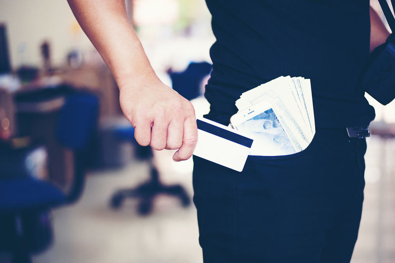 Midsection Of Businessman With Paper Currency In Pocket Holding Credit Card