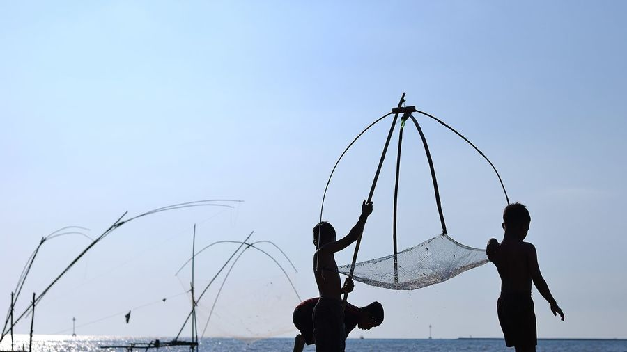 Shirtless Boys With Fishing Equipment Against Sky