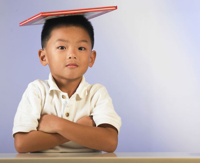 Portrait of boy balancing book while sitting with arms crossed at table against wall