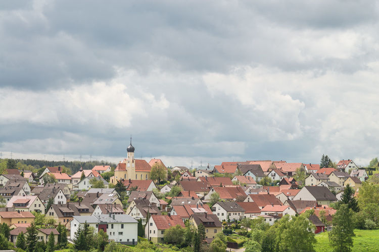 Houses in town against cloudy sky
