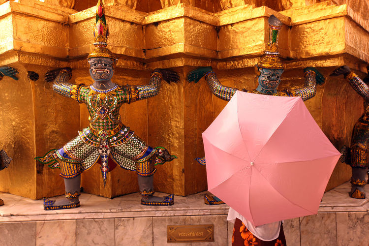 Person with umbrella by buddhist temple