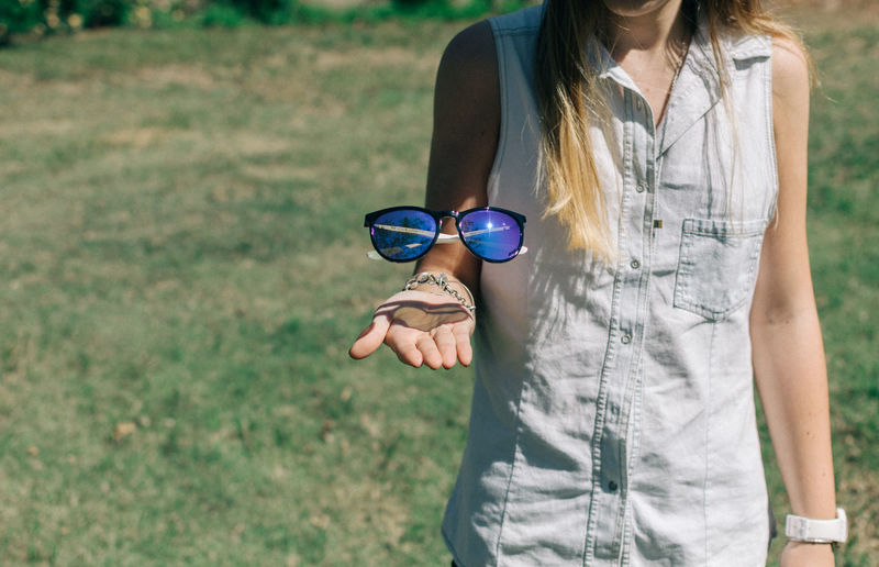 Midsection of woman levitating sunglasses
