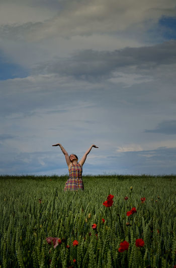 Young woman with arms raised standing amidst plants on field against sky