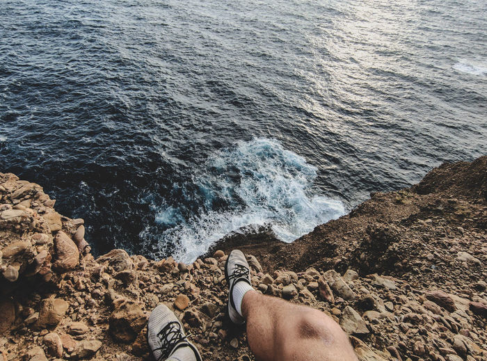 Low section of man on rock at beach