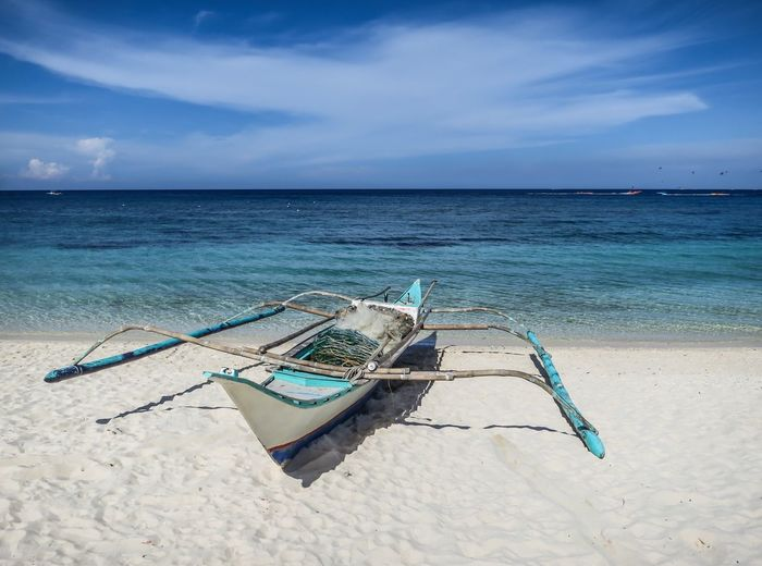 Waiting by the Sea for its fishermen riders. Beach Photography Done That. White Sand Beach Beach Beauty In Nature Cloud - Sky Day Fishing Boat Horizon Over Water Moored Nature Nautical Vessel No People Outdoors Outrigger Sand Scenics Sea Shore Sky Transportation Water Lost In The Landscape
