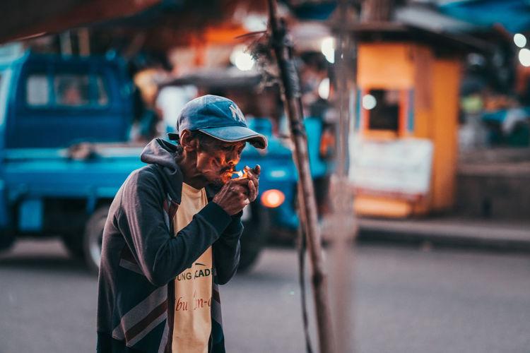 Man holding umbrella standing on street in city