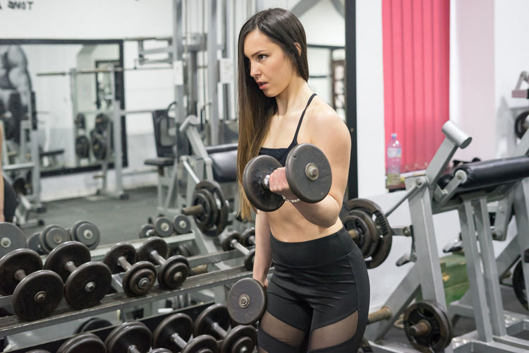 Adult Bicep Body Conscious Dumbbell Effort Equipment Exercise Equipment Exercising Gym Health Club Healthy Lifestyle Indoors  Lifestyles Muscular Build One Person Sport Sports Training Strength Weight Weight Training  Weights Women Young Adult Young Women