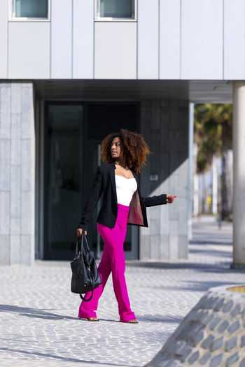 Front view of young beautiful curly woman wearing elegant clothes and handbag while standing in the street in sunny day Architecture Building Exterior One Person Built Structure Real People City Full Length Women Hair Day Young Adult Lifestyles Adult Leisure Activity Happiness Footpath Curly Hair Front View Hairstyle Outdoors Human Arm Standing Posing Model Handbag  Afro African American Smiling Laughing Looking At Camera Looking Away Elegant Attractive Bussinesswoman Empowered City Life Urban Walking Beautiful Pink
