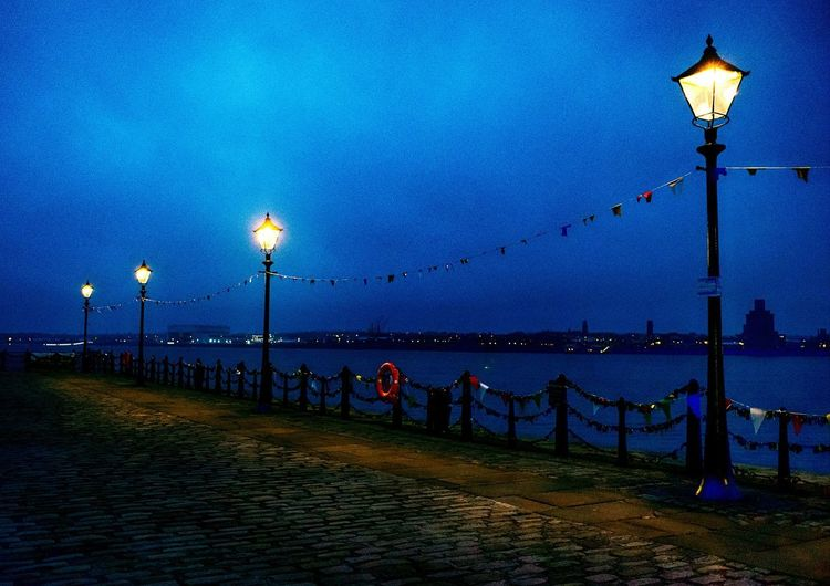 Illuminated street lights by river against clear sky at night