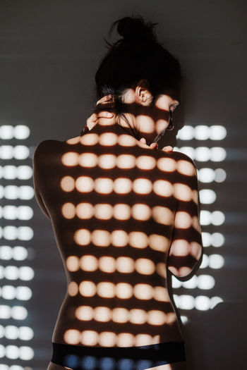 Rear view of woman standing against illuminated wall