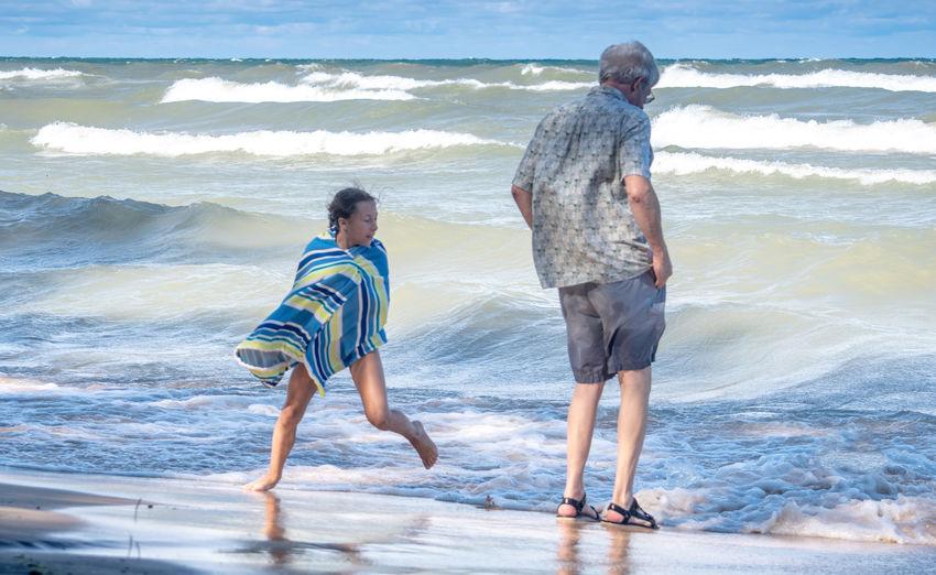 Rear view of friends walking on beach