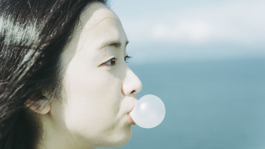Close-up of beautiful woman blowing bubble gum