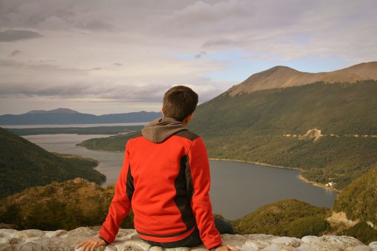 Rear View Of Man Sitting On Cliff Lake And Mountains Against Cloudy Sky