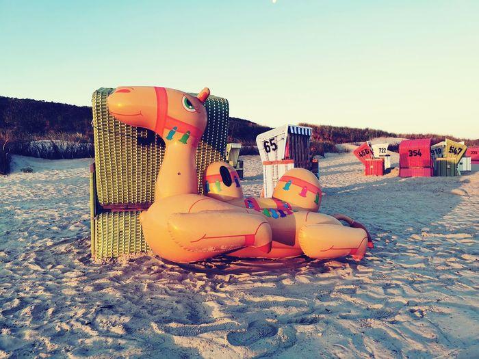 Stuffed toy on beach against clear sky