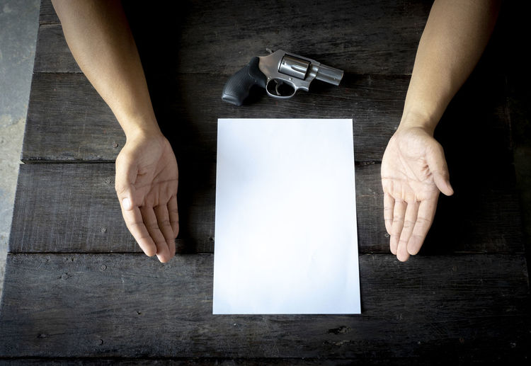 Close-up of businessman with gun and paper on table