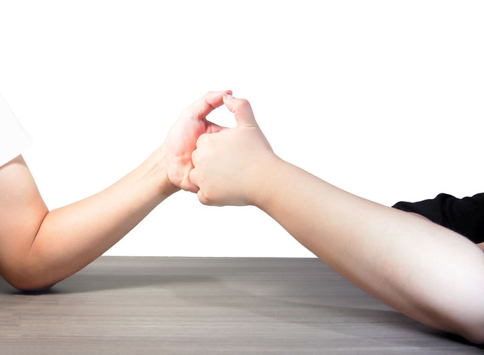 Two hands tag team against white background Hands Two People Togetherness Tag Teamwork Love Friends Holding Hands Touching Positive Emotion Symbol Gesturing Isolated White Background Studio Shot Concept Arm Close-up Communication Fingers Joint Connection Cheers Care Partnership Cooperation