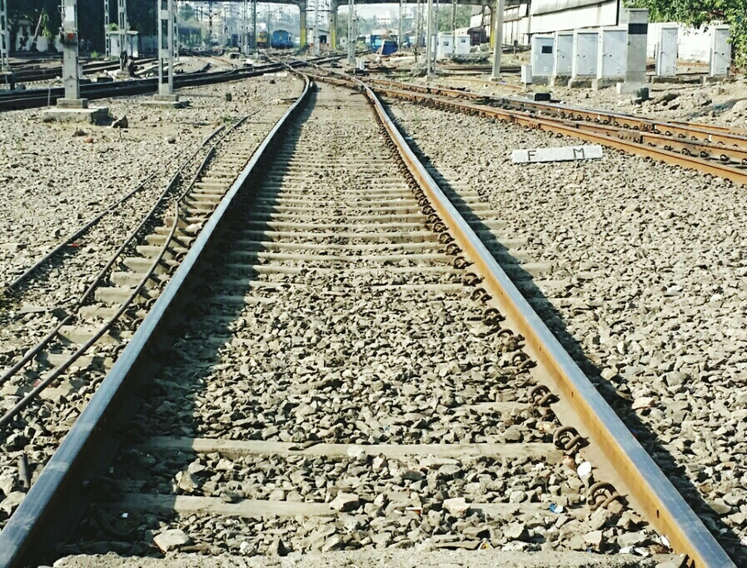 railroad track, rail transportation, transportation, the way forward, diminishing perspective, built structure, public transportation, vanishing point, high angle view, architecture, railway track, railroad station platform, railroad station, stone - object, building exterior, day, outdoors, metal, gravel, connection