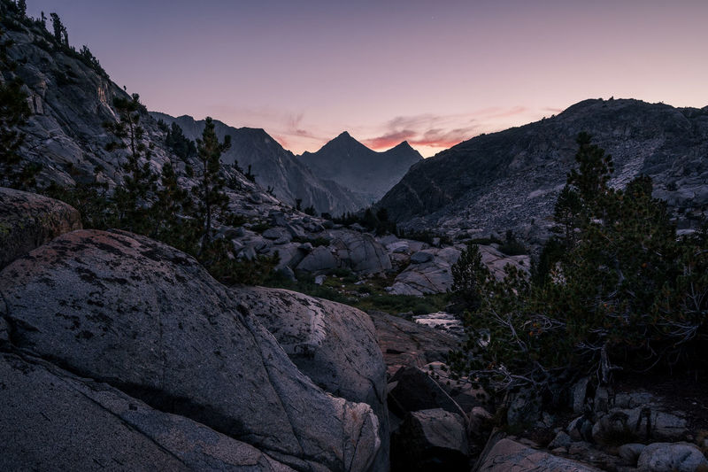 Time to embrace darkness | JMT DAY 19 - TWILIGHT AT PALISADE LAKES Twilight at Palisade Lakes Once the sun was set behind Mt. Shakspere (12,174 ft), the whole world slowly started sinking into oblivion. Although a few bright smudges of clouds lingered right above the peak, it soon faded as quickly as it radiated. Just like that. A bit of blue hour light still lingering, what came next was stillness that I wasn't anticipating. Everything seemed frozen. As if the world stopped turning. As if time just stood still. As if the whole mountain range stopped sprawling. Twilight was lurking. And nothing else was disturbing the sound of wind. And just like that, the feeling of tiredness and anxiety subsided. As if nothing mattered from this point on. And it was time to embrace darkness all around me. Palisade Lakes, Kings Canyon National Park, CA Mountain Mountain Range Scenics - Nature Beauty In Nature Sky Rock Tranquil Scene Tranquility Rock - Object Nature Non-urban Scene Landscape No People Sunset Idyllic Physical Geography Geology Outdoors Mountain Peak Palisade Lakes, Kings Canyon National Park, CA JMT Pct Wilderness Adventure