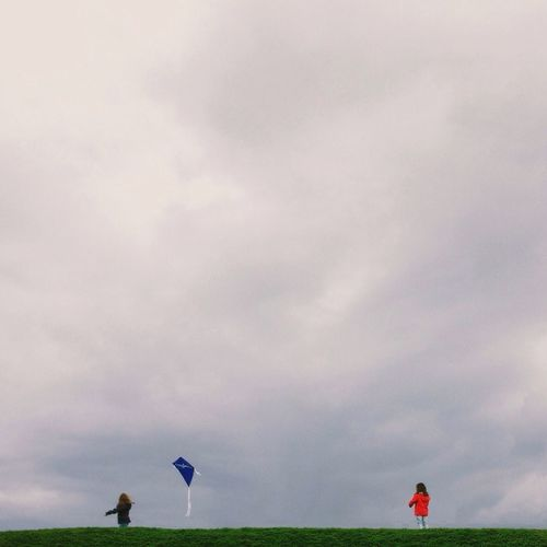 People on grassy field against cloudy sky