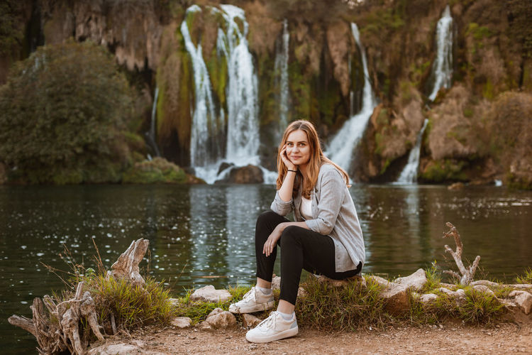 Young woman sitting on rock by waterfalls