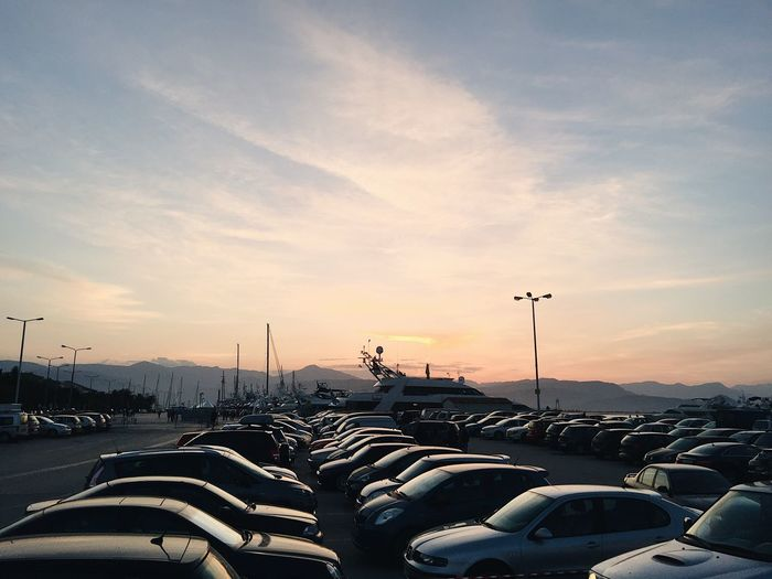 Cars in parking lot against sky during sunset
