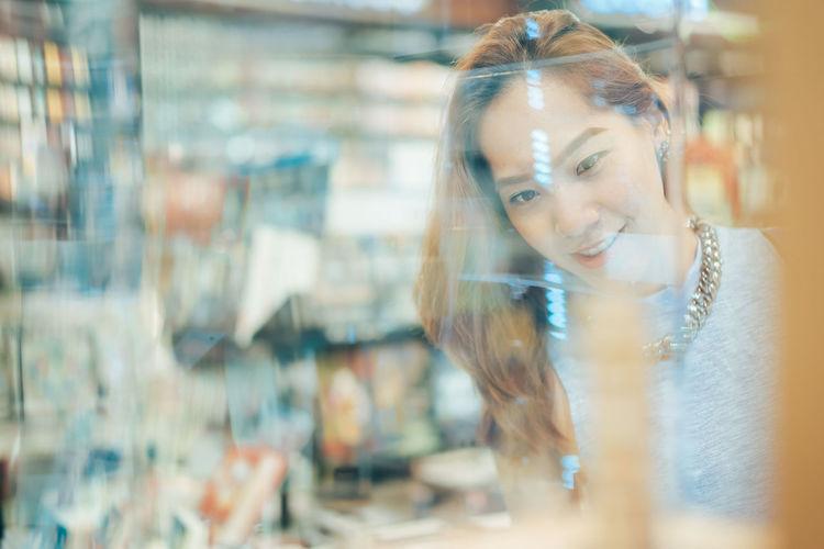 Woman In Shopping Mall Seen Through Glass Window