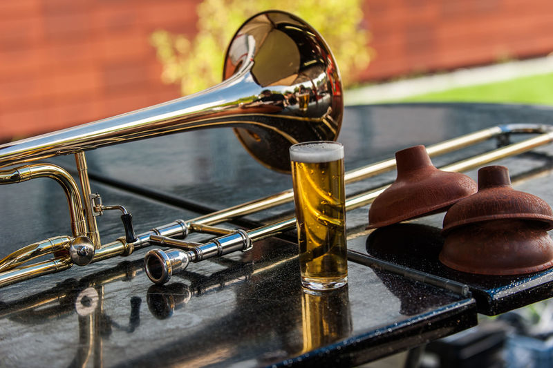 Close-up of trombone by beer glass on table