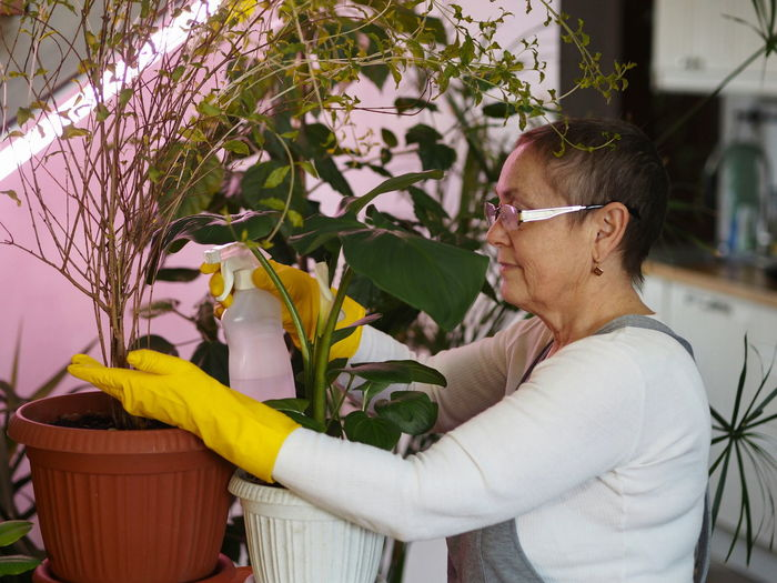 Side view of woman spraying water on plants