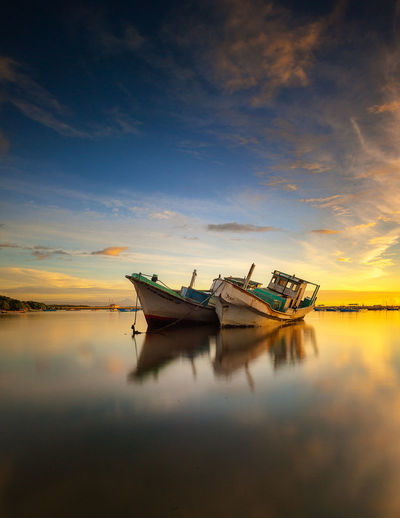 Fishing boats moored in sea against sky during sunset