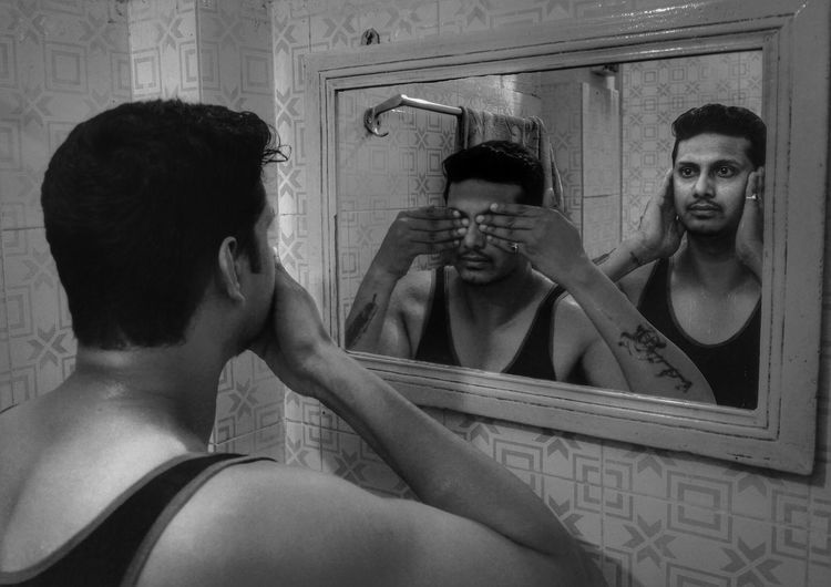 Multiple image of man reflecting on mirror in bathroom