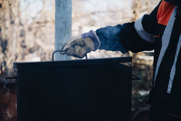 Midsection of man holding tool box outdoors
