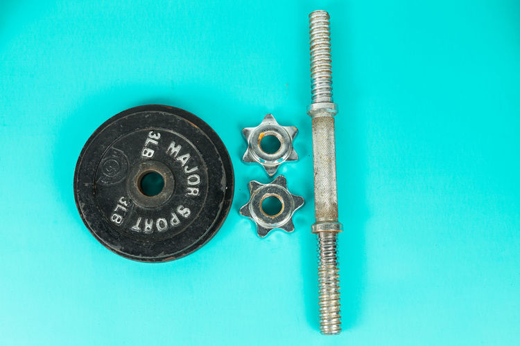 Directly above view of weights on turquoise background