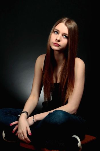 Thoughtful young woman sitting against black background