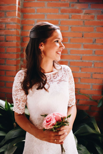 Smiling woman holding flowers while standing against brick wall