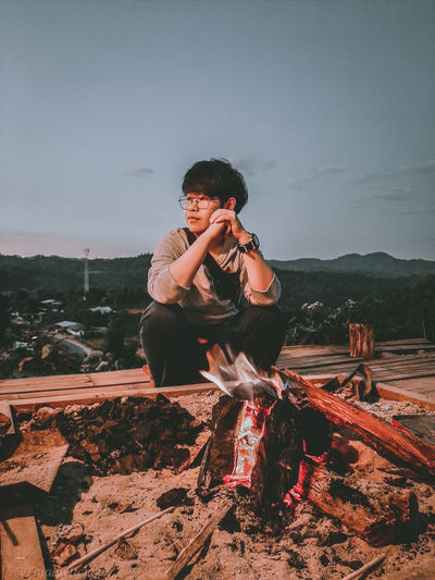 Young man sitting on mountain against clear sky