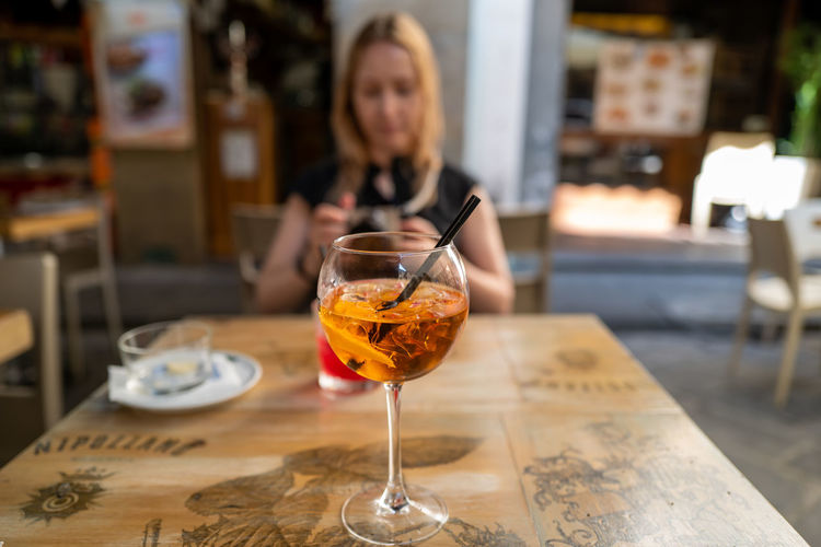 Woman with drink on table in restaurant