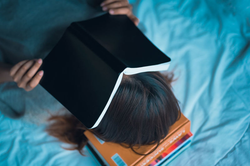 young women lie down on pile of book and cover her face by the book education and growth concept