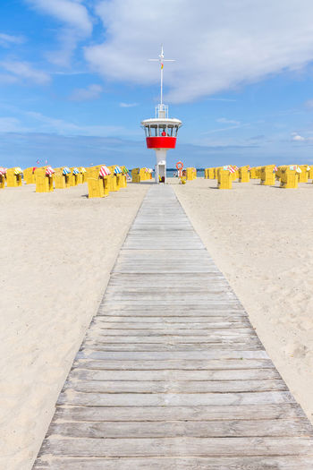 Lookout Tower Amidst Hooded Chairs At Beach Against Sky