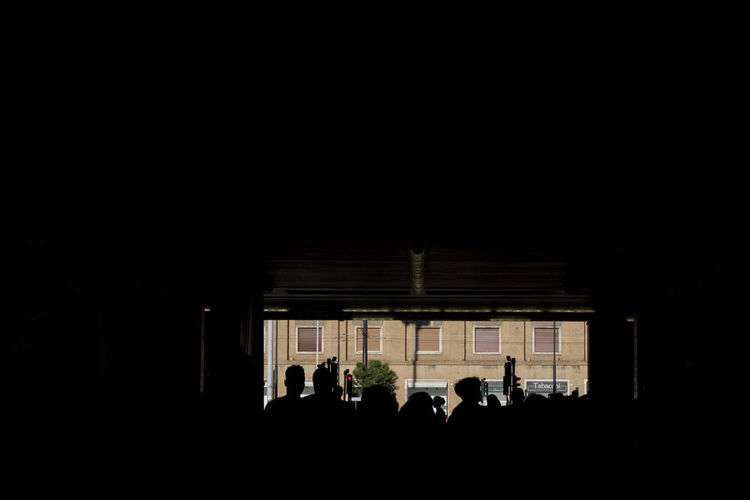 Silhouette people in illuminated building at night