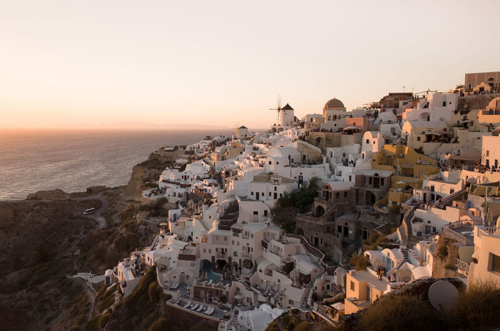 Oia Santorini Architecture Building Building Exterior Built Structure City Cityscape Clear Sky Community Crowd Crowded High Angle View House Nature Outdoors Residential District Santorini Sea Sky Sunset Town TOWNSCAPE Travel Destinations Water
