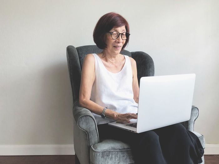 Senior Woman Using Laptop On Chair At Home