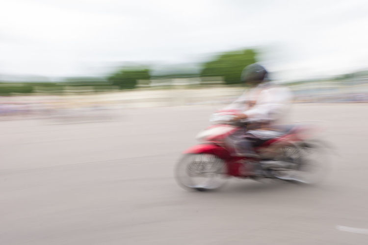 Blurred motion of man riding motorcycle on road against sky