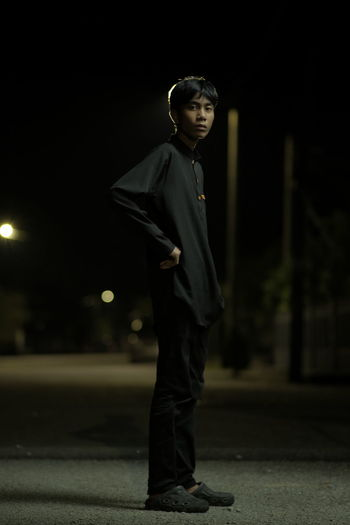 Full length of boy looking at illuminated city at night