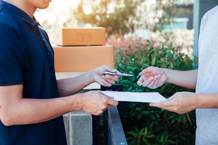 Midsection of delivery person giving customer document to sign
