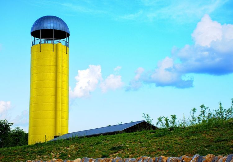 Low angle view of barn and yellow silo against sky