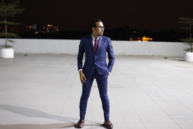 Full length of businessman standing on paved footpath at night