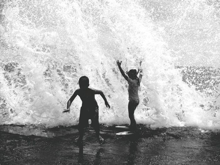 Children playing under splashing wave