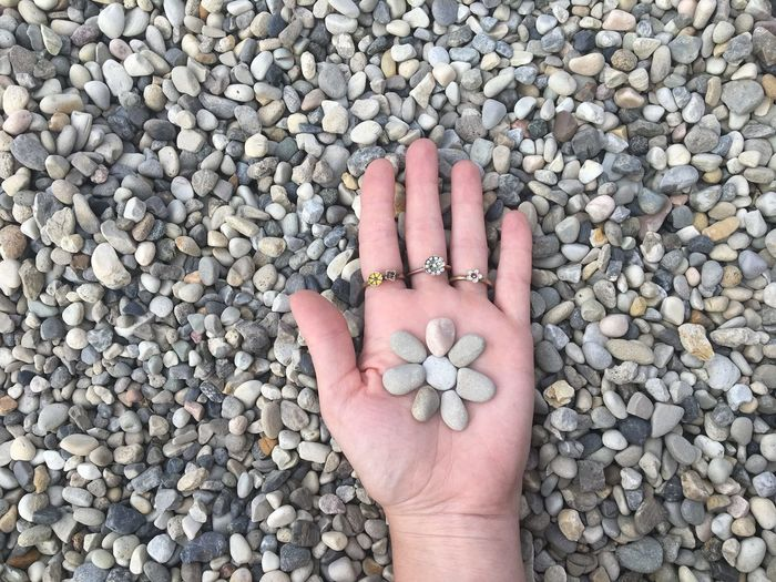Cropped hand holding pebbles
