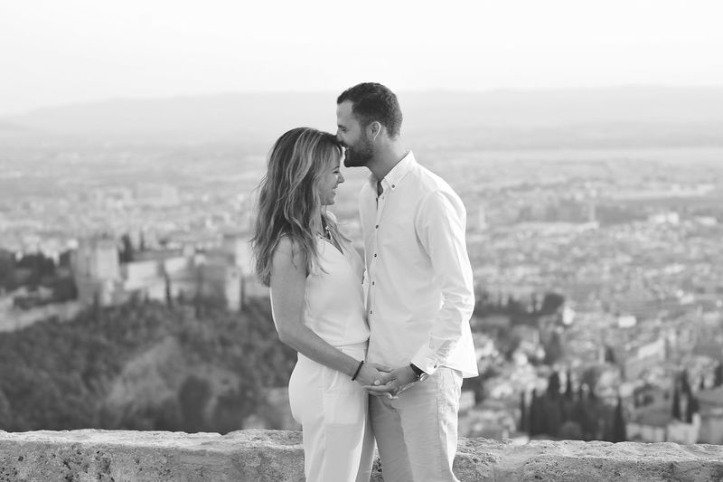 Side view of young romantic couple standing by retaining wall