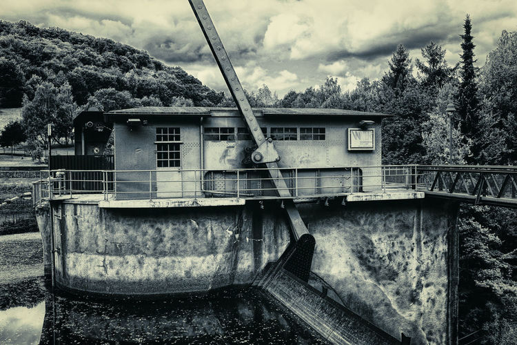 Abandoned boat by river against sky